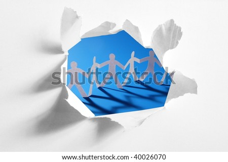 chain of paper man in a hole showing teamwork - stock photo