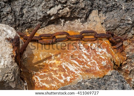 Chain ruined by time and rust on a beach - stock photo