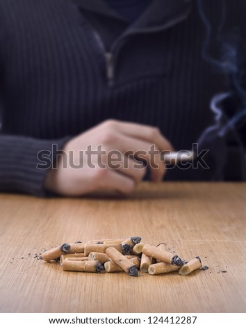 chain smoking, pile of cigarette butts on table with person smoking in background - stock photo
