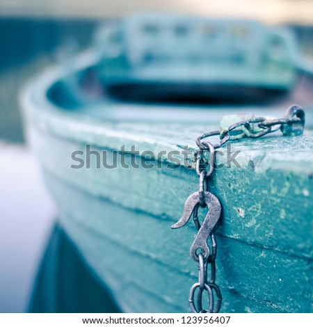 Chained wooden boat is waiting for sunday passengers. Focus is on the hook and the boat in background is blurry. - stock photo