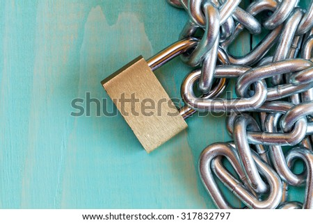 Chains and padlock on the blue wooden background - stock photo