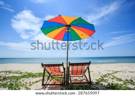 chair and colorful umbrella on the beach  - stock photo
