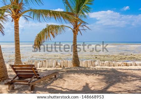Chair and green trees on a white sand beach. Watamu, Kenya - Africa - stock photo