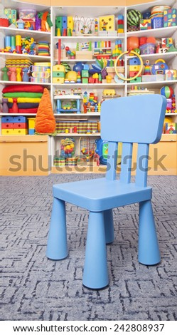 Chair and shelf with many colored toys - stock photo
