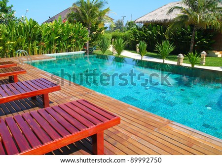 chair and swimming pool surrounded by  tropical plants - stock photo