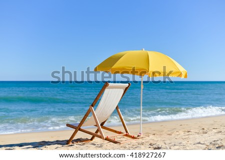 Chair and umbrella on stunning tropical beach vacation background - stock photo