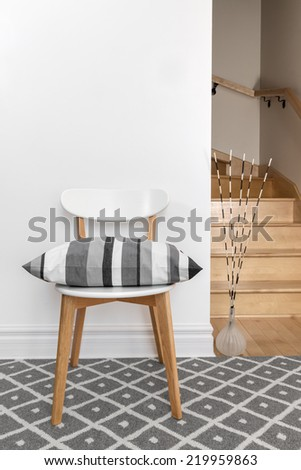 Chair decorated with gray striped cushion in a room with staircase. - stock photo