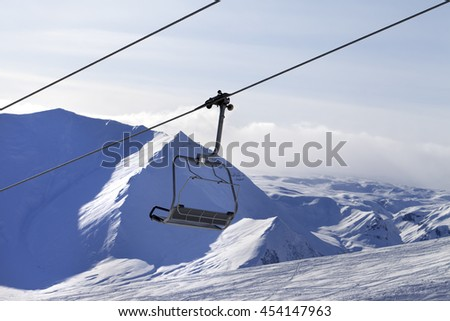 Chair lift and mountains in evening. Caucasus Mountains, Georgia, ski resort Gudauri. - stock photo