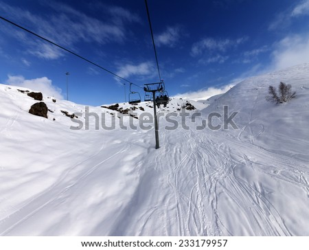 Chair-lift and off-piste slope in sun day. Caucasus Mountains, Georgia, ski resort Gudauri. Wide angle view. - stock photo