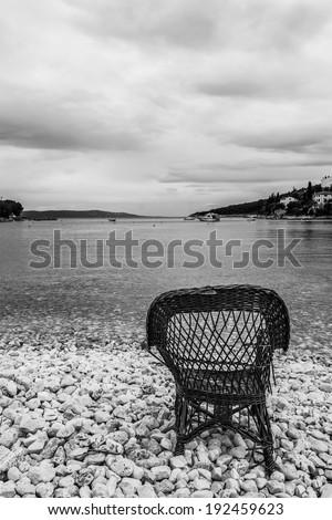 Chair on a beach covered with pebbles, Santa Marina, Istra, Croatia - stock photo