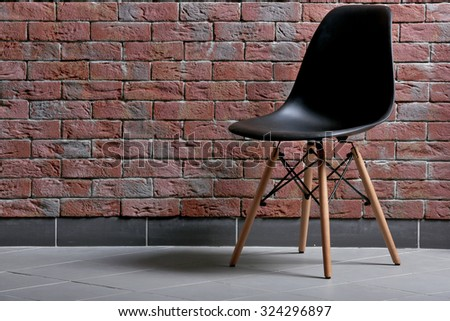 Chair on brick wall background - stock photo