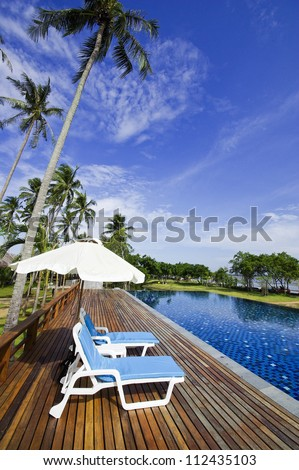 Chair on swimming pool beside the beach - stock photo