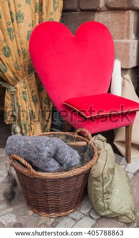 chair with back in the form of heart, standing against the wall, near the basket with yarn - stock photo