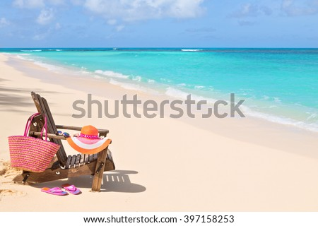 Chair with bag, hat, flip-flops and sunglasses on sunny beach, tropical beach vacation and travel concept - stock photo