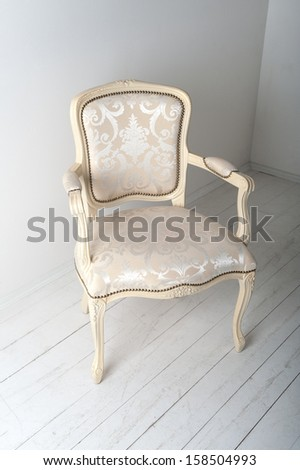 chair with luxurious upholstery in plain white interior - stock photo