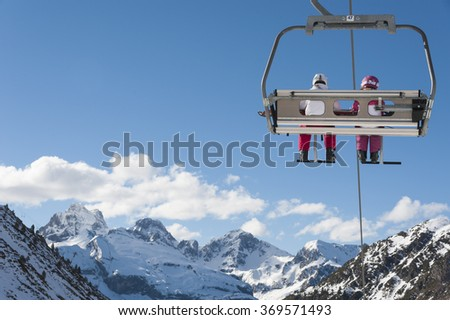 Chairlift full of skiers at a ski resort, with snowy mountains on background - stock photo