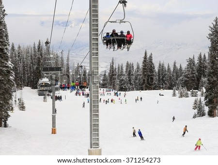 Chairlift taking skiers and snowboarders up the slope; people skiing underneath it - stock photo