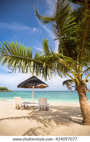 Chairs and parasol at tropical beach with coconut palms - stock photo