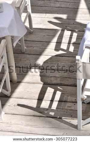 chairs and tables shadows on wooden floor - stock photo
