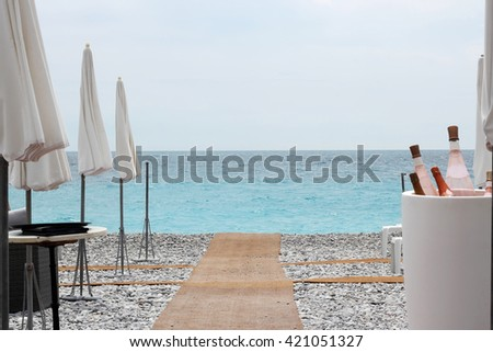 Chairs and tables with wine bottle on Nice beach along Promenade des Anglais, luxury view, summer vacation concept - stock photo
