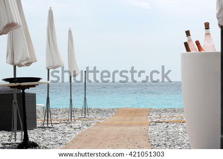 Chairs and tables with wine bottle on Nice beach, luxury view, summer vacation concept - stock photo