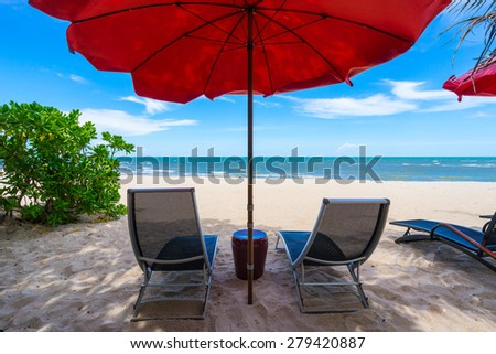 Chairs and umbrella on a beautiful tropical beach in Thailand - stock photo