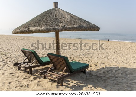 Chairs and umbrella on a tropical beach - stock photo