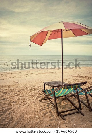 chairs and umbrella on the beach (retro style) - stock photo