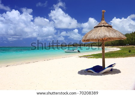 chairs and umbrella on tropical beach - stock photo