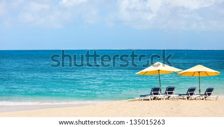 Chairs and umbrellas on a beautiful Caribbean beach - stock photo