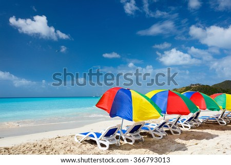 Chairs and umbrellas on a beautiful tropical beach at Caribbean - stock photo