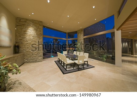 Chairs around table on rug in spacious dining room at home - stock photo