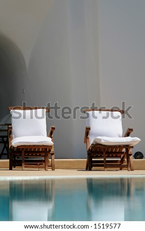 Chairs at the swimming pool at Santorini Greece - stock photo