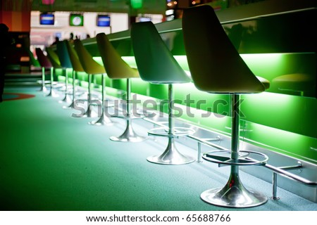Chairs in row in bar with green lights - stock photo