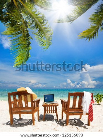 Chairs, laptop and put away tie and white collar shirt, straw hat. Chairs and table on the beach on sunny day - stock photo