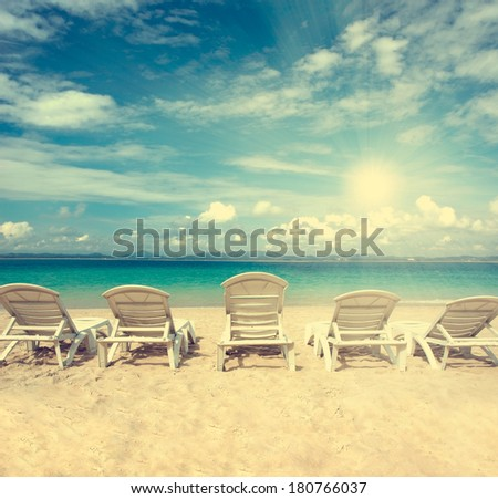 chairs on beach with blue sky for summer holiday vintage retro filter  - stock photo