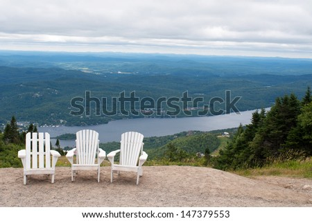 Chairs on top of mountain  at a ski resort during summer time depicting relaxing concept - stock photo