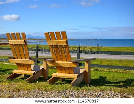Chairs set on the beach overlooking the ocean - stock photo