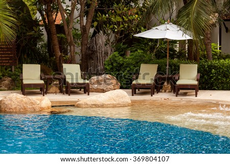 chairs stand near the swimming pool of the hotel territory - stock photo