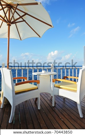 Chairs, table and umbrella on the balcony of the villa near the sea - stock photo