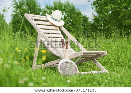 Chaise-longue with a hat and badminton rackets in the middle of the meadow  - stock photo