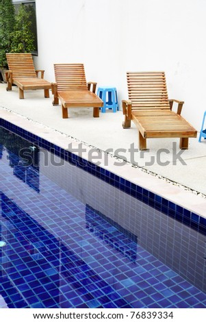 Chaise-longues near pool at tropical resort - stock photo