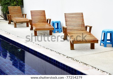Chaise longues near swimming pool at tropical resort - stock photo