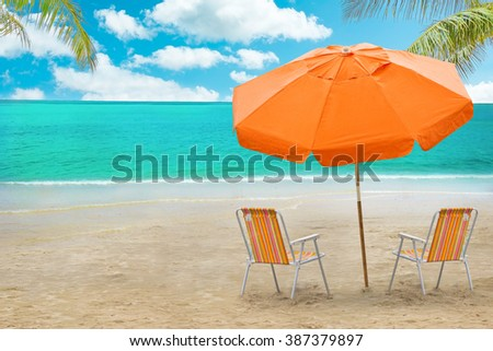 Chaise lounge and umbrella on beach - stock photo