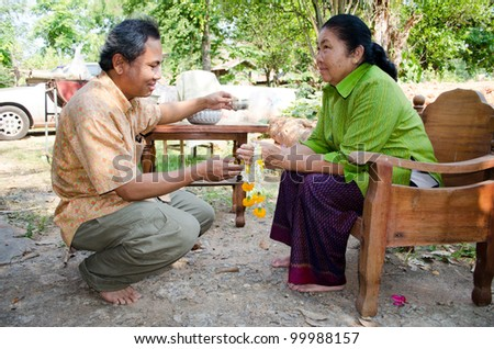 CHAIYAPHUM, THAILAND - APRIL 13: Thai people celebrate Songkran (new year / water festival: 13 April) by giving garlands to their seniors and asked for blessings on April 13, 2012 in Nakhonratchasima, Thailand. - stock photo