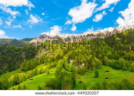 Chalets on green mountain slope. Swiss Alps. Lauterbrunnen, Switzerland, Europe. - stock photo