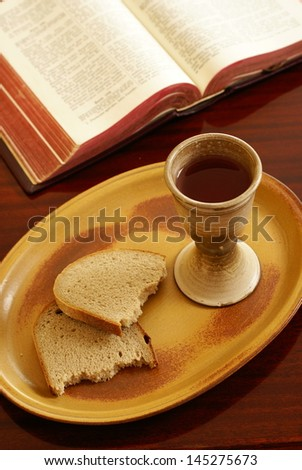 Chalice, bread and open Bible on a table. - stock photo