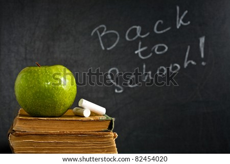 Chalk and green apple on old textbook against blackboard with text BACK TO SCHOOL in class. School concept - stock photo