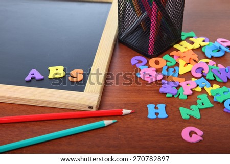 Chalk board, letters and pencils on a wooden table close-up - stock photo