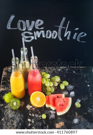 Chalk Drawing Love Smoothie Tall Bottles Yellow Red Green Tropical Fruits Juices Water Melon Kiwi Grape Orange Mango Black Background Selective focus - stock photo
